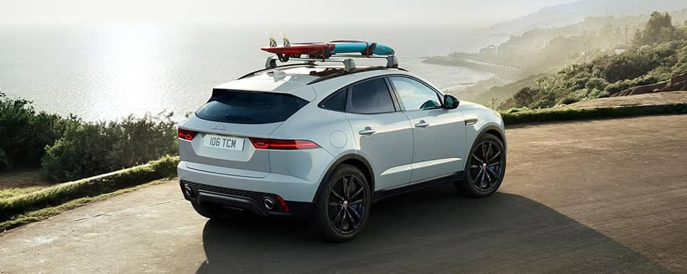 2018 Jaguar E-PACE driving by the ocean with surf boards on roof rack
