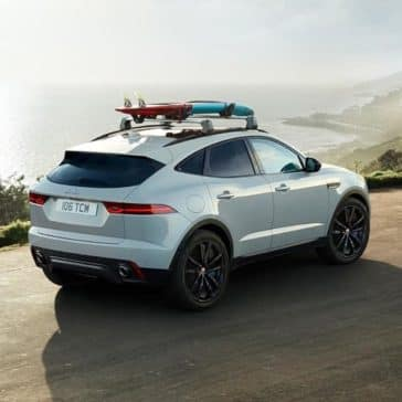 2019 Jaguar E-PACE Driving Along Ocean with Surfboard on Roof Rails