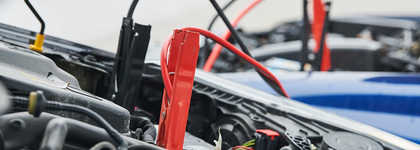 Automobile road assistance or help. engine starting problem. Car battery discharged. Charging by booster jumper cables
