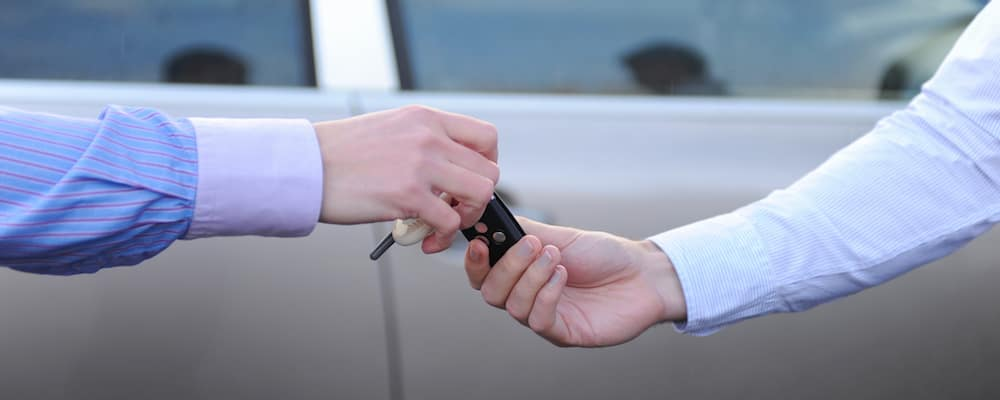 Person handing keys over to another person