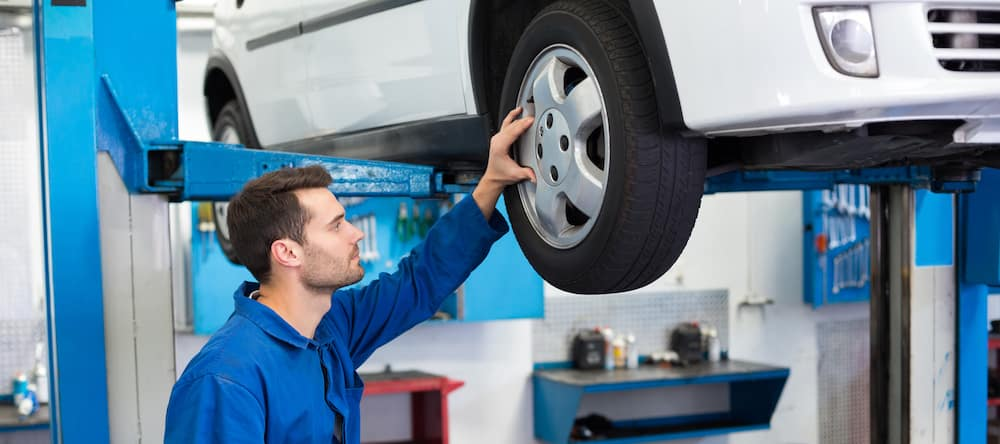 Mechanic looking at car tire in garage