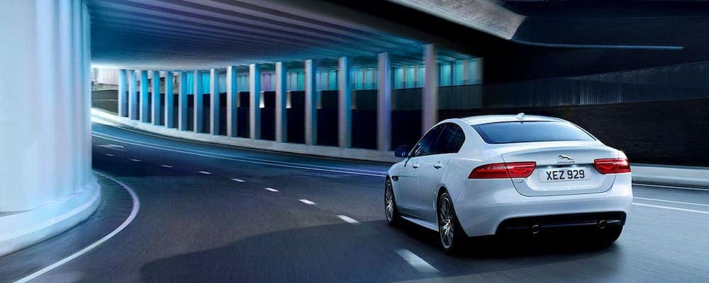 2019 Jaguar xe in white driving through highway underpass