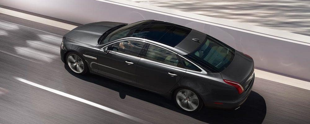 gray 2019 jaguar XJ with panoramic roof driving on highway