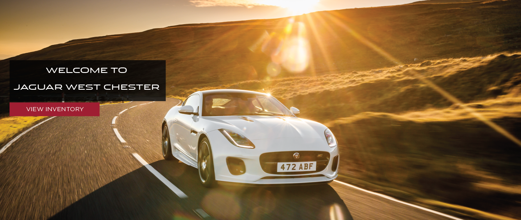 Alt Text: WELCOME TO JAGUAR WEST CHESTER_VIEW INVENTORY_IMAGE DISPLAYING WHITE 2020 JAGUAR F-TYPE DRIVING DOWN ROAD NEAR SUNSET