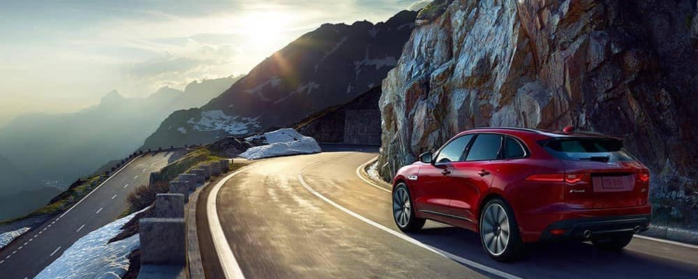 2019 Jaguar F-PACE in red driving on snowy mountain highway