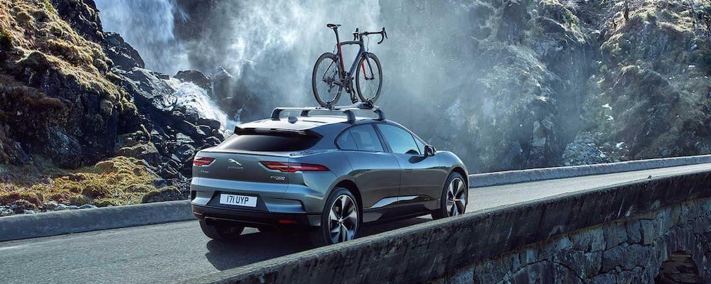 2019 Jaguar I-PACE driving on mountain bridge with roof-mounted bicycle