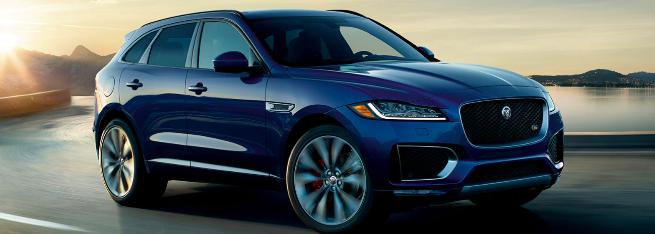 A pre-owned Jaguar F-Pace driving on a road by a lake