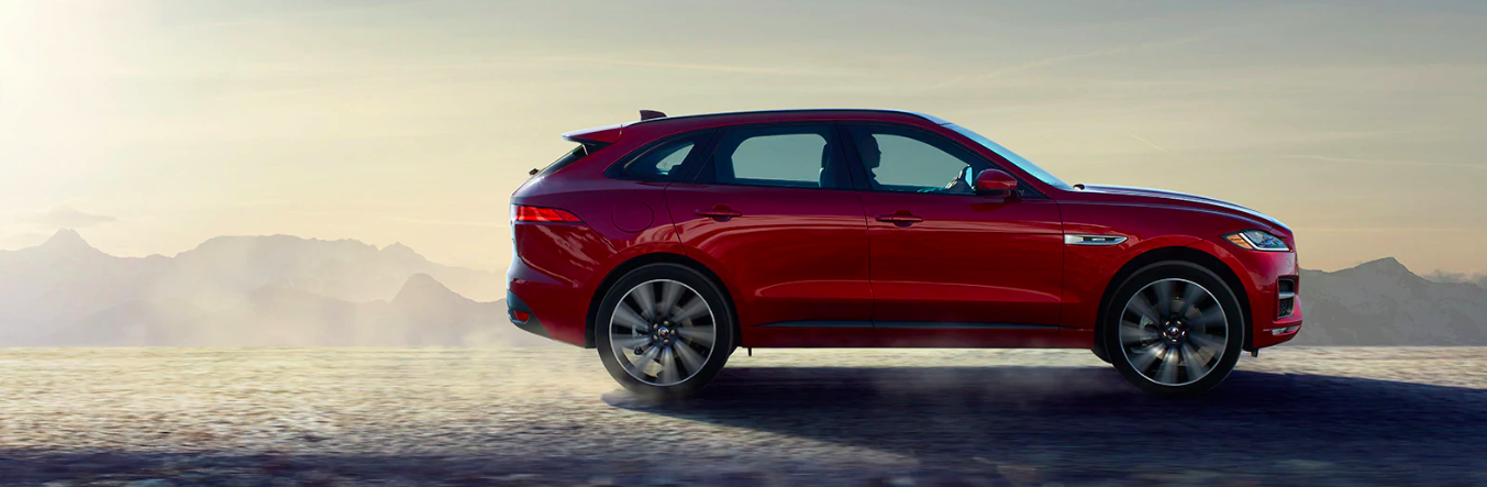 Profile view of a 2020 Jaguar F-PACE driving on sand in a desert