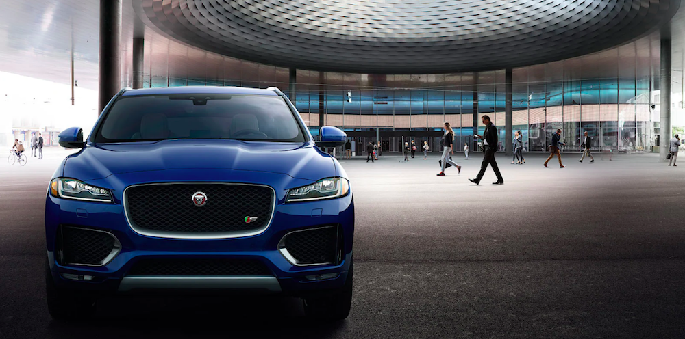 Blue Jaguar F-PACE parked with people walking in background