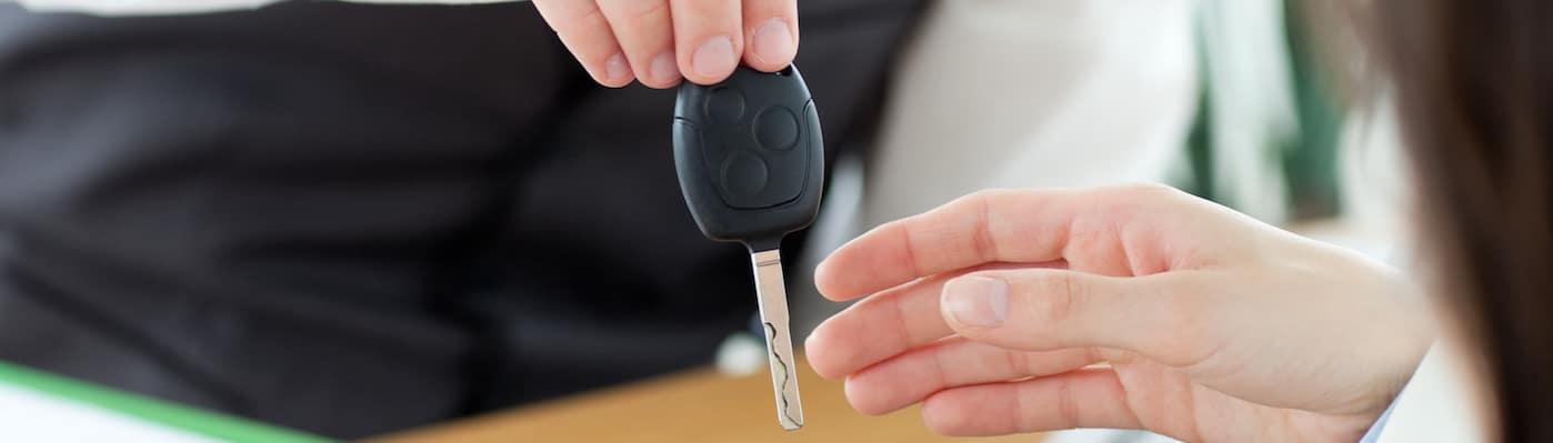 Salesperson handing car keys to customer