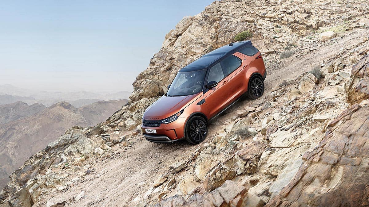 2018 Land Rover Discovery driving down gravel hill