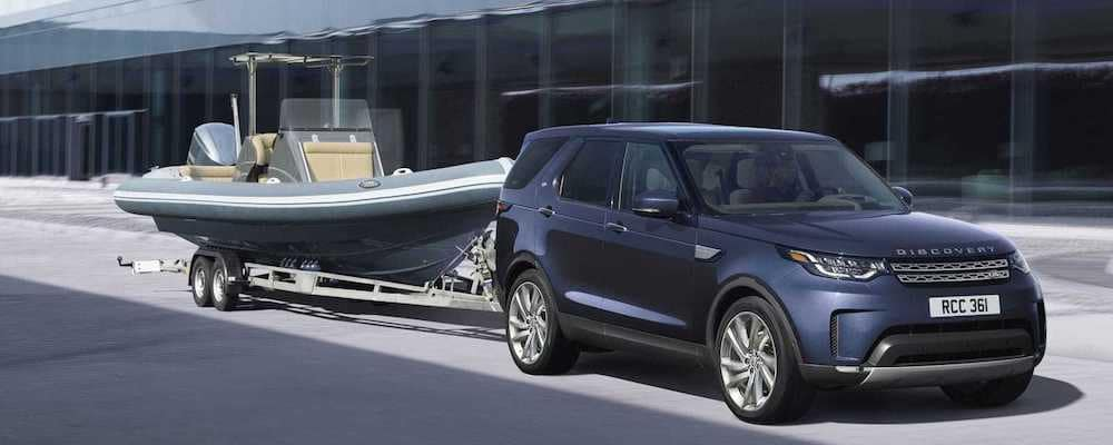 2019 land rover discovery in blue towing a small boat