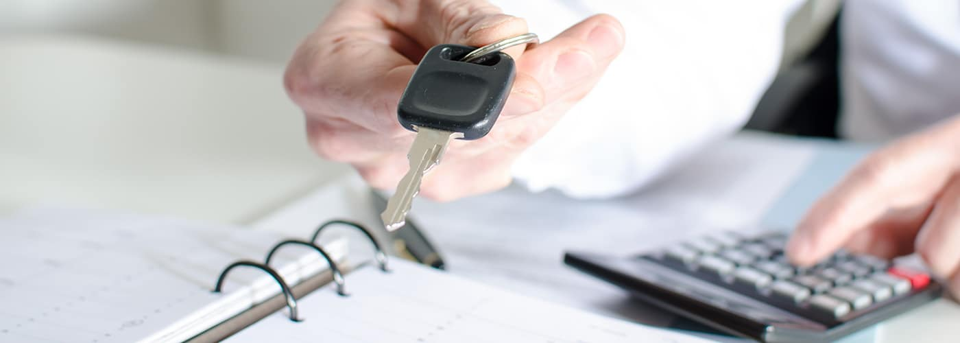 Car salesman holding a key and calculating a price at the dealership office