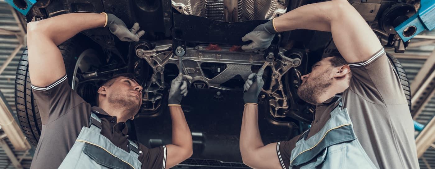 auto mechanics working under lifted vehicle