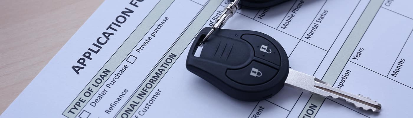 Application form for car loan and key on wooden table, close up