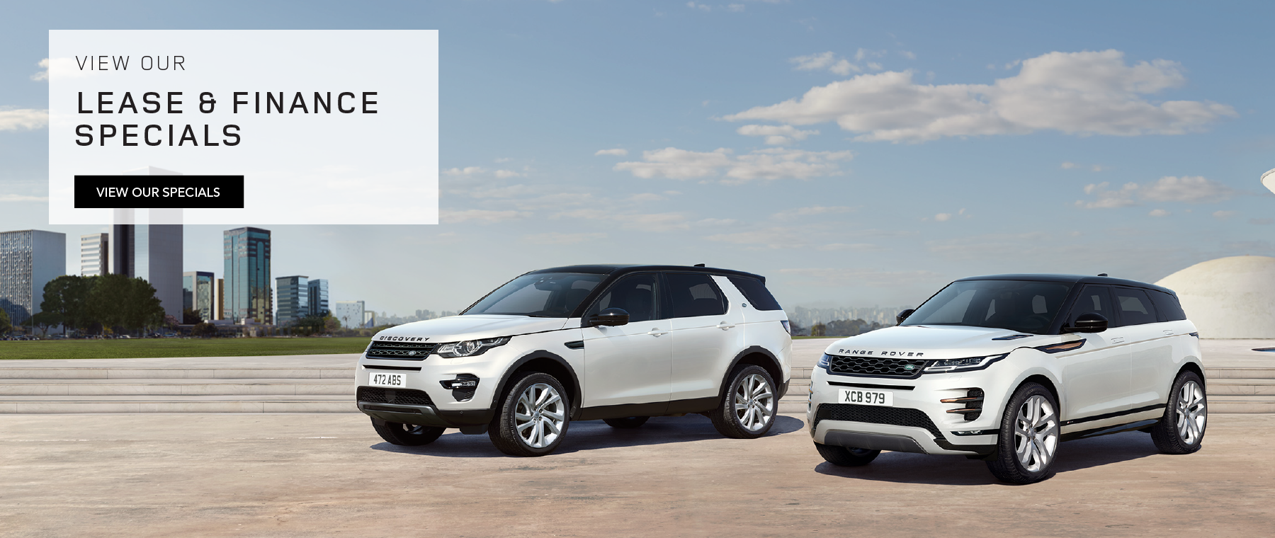 LAND ROVER DISCOVERY SPORT AND RANGE ROVER EVOQUE PARKED ON CENTER WITH GRASS, CLOUDY BLUE SKIES AND CITY SKYLINE IN BACKGROUND. VIEW OUR LEASE AND FINANCE SPECIALS. VIEW OUR SPECIALS.