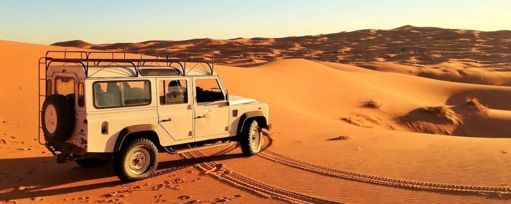 Land Rover Defender parked in desert landscape
