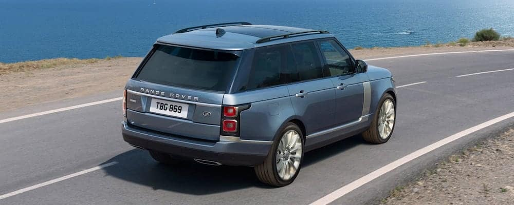 blue 2019 range rover driving on coastal highway