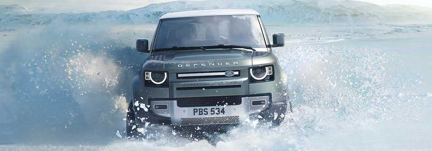 A 2020 Land Rover Defender driving through a snow drift in winter