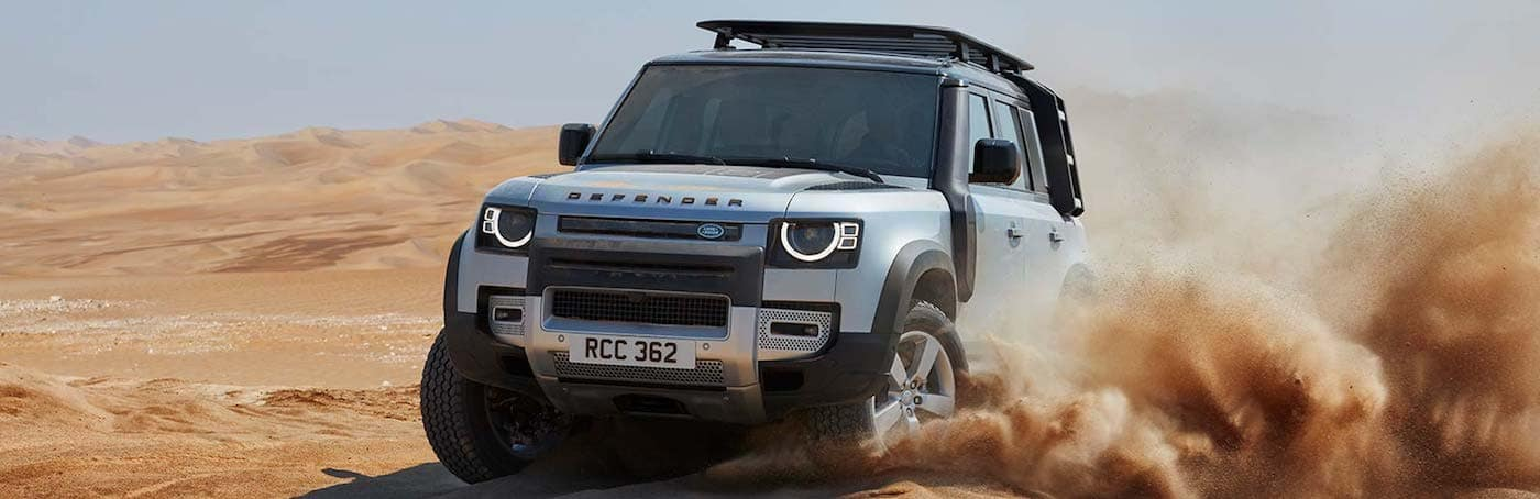 A 2020 Land Rover Defender driving through sand dunes