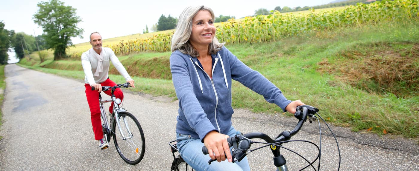A couple riding bikes on a country road