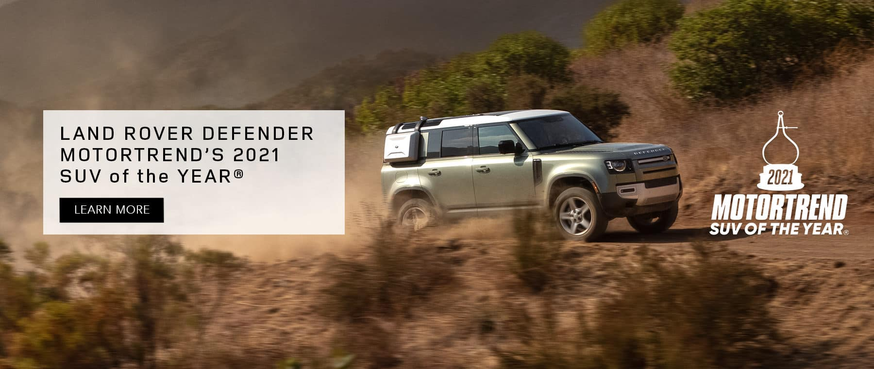 LAND ROVER DEFENDER. MOTORTREND'S 2021 SUV OF THE YEAR. LEANR MORE. SILVER LAND ROVER DEFENDER DRIVING DOWN DIRT ROAD.