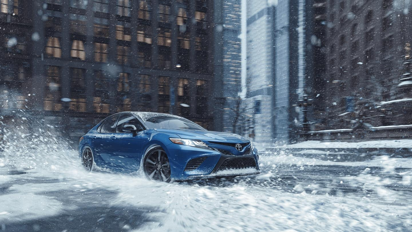 blue camry driving in puddle