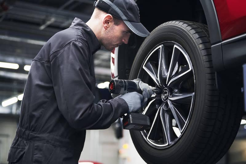 Technician tightening tire with drill