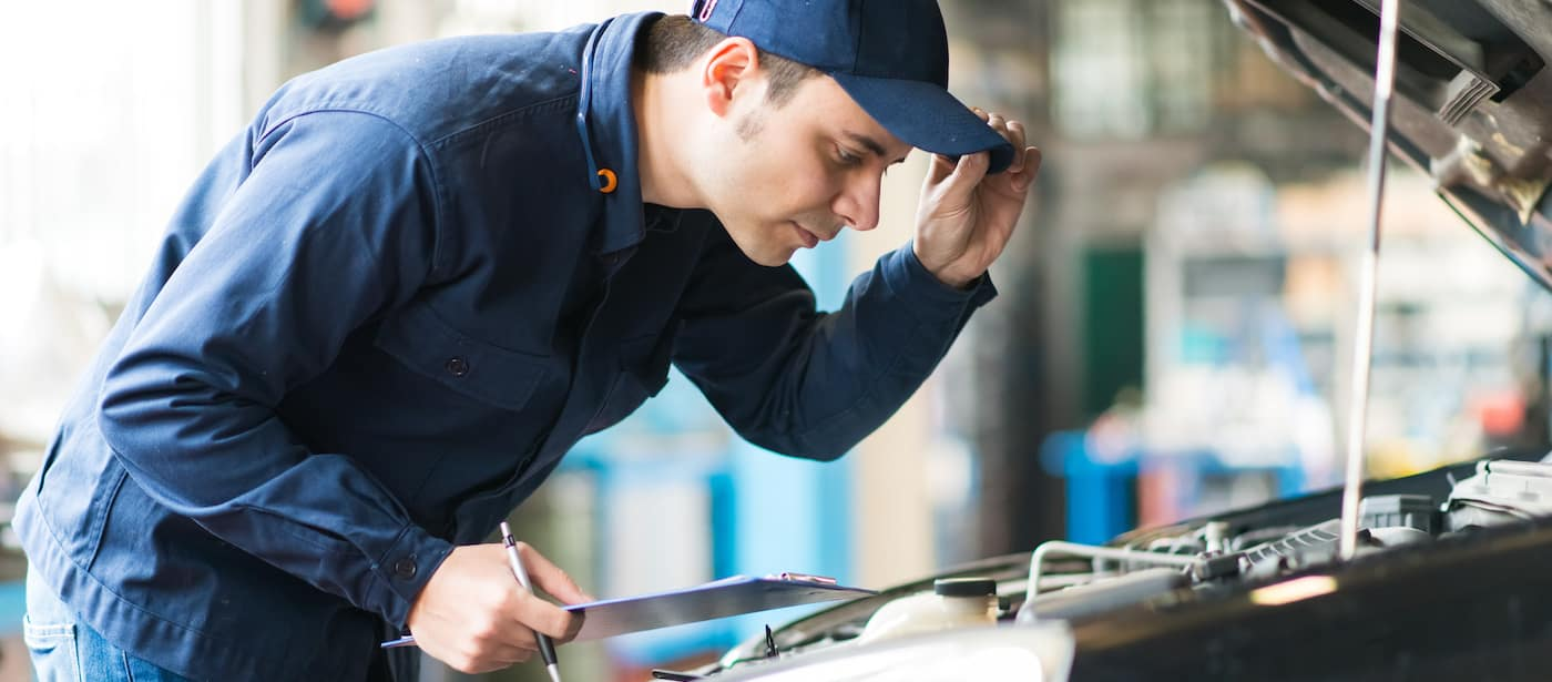 Mechanic with hat inspecting engine