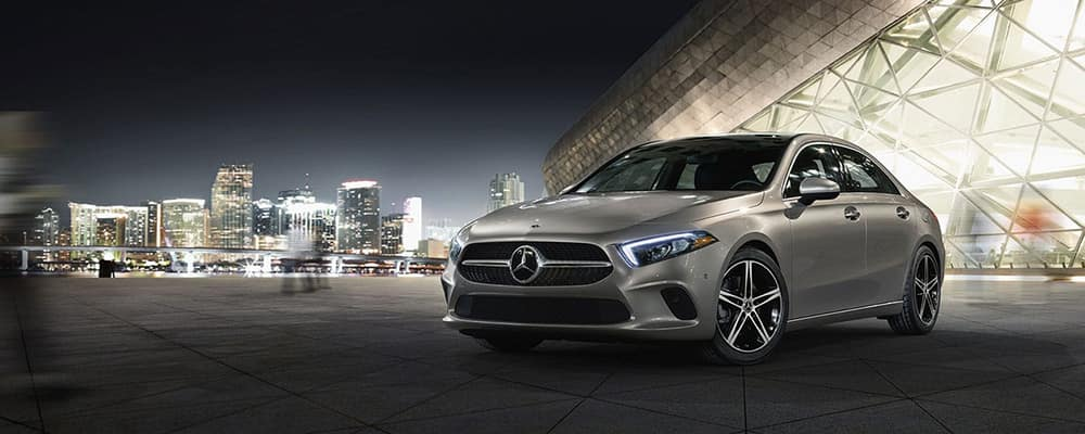 Silver 2021 A-Class parked in front of a city skyline at night