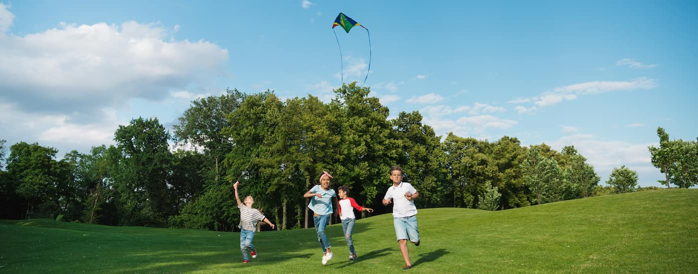 Children in park playing with kite
