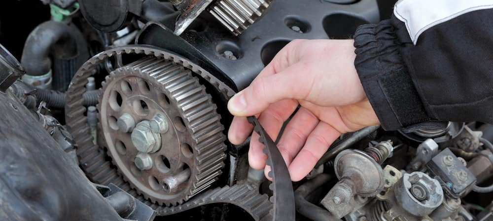 hand repairing timing belt on engine
