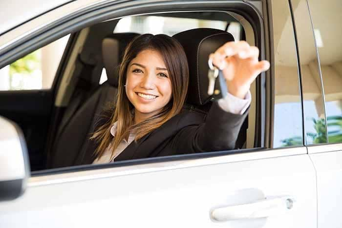 Woman holding car keys to new car