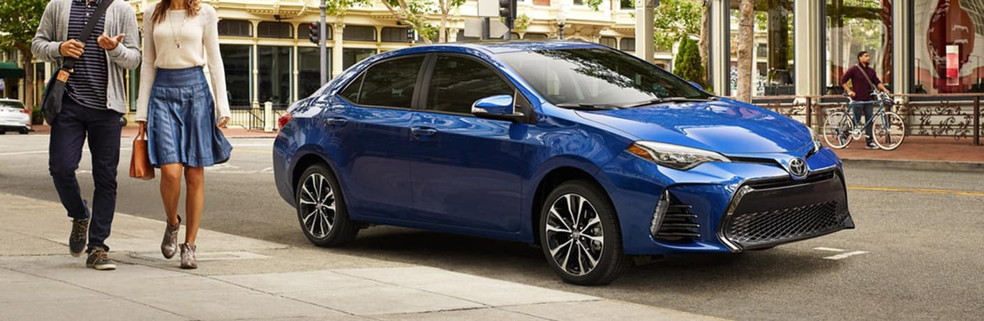 Image of a blue 2019 Toyota Corolla parked on a city street with a couple walking away from it.