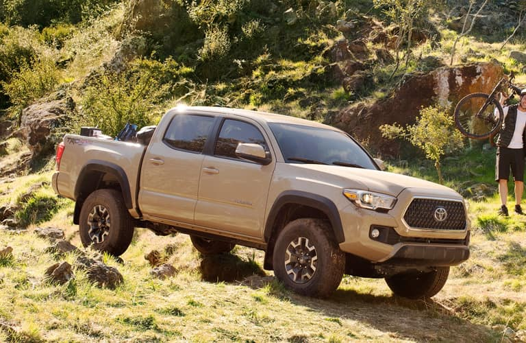 Image of a tan 2019 Toyota Tacoma truck driving down a grassy hill.