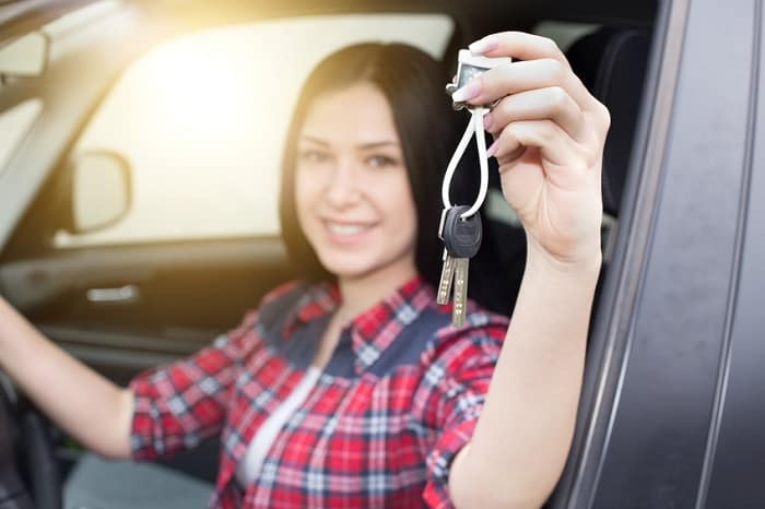 Image of a young woman holding her car keys inside a new sedan.
