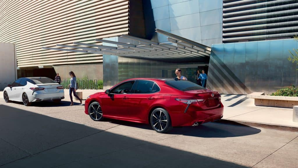 Image of a red Toyota Camry parked in front of a glass building.