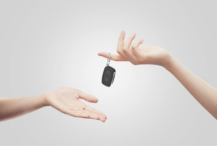 Image of hands exchanging car keys against a gray background