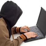 Hacker in the front of a laptop computer