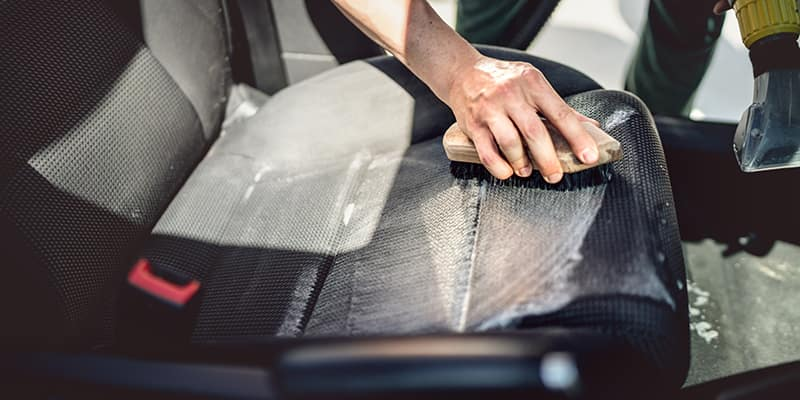 Scrubbing leather seats with brush