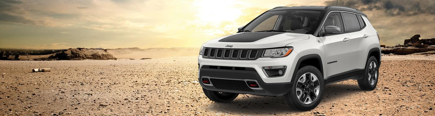 A white Jeep Compass parked in the desert