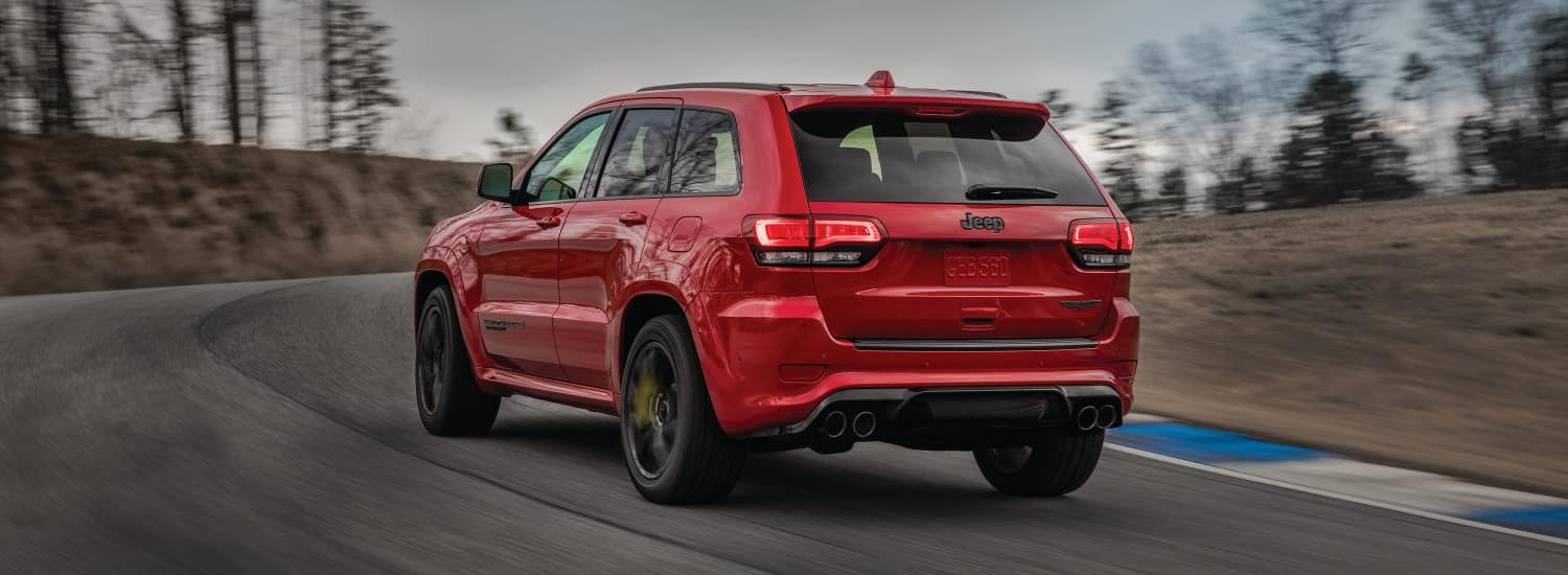 A red 2018 Jeep Grand Cherokee driving around a curve