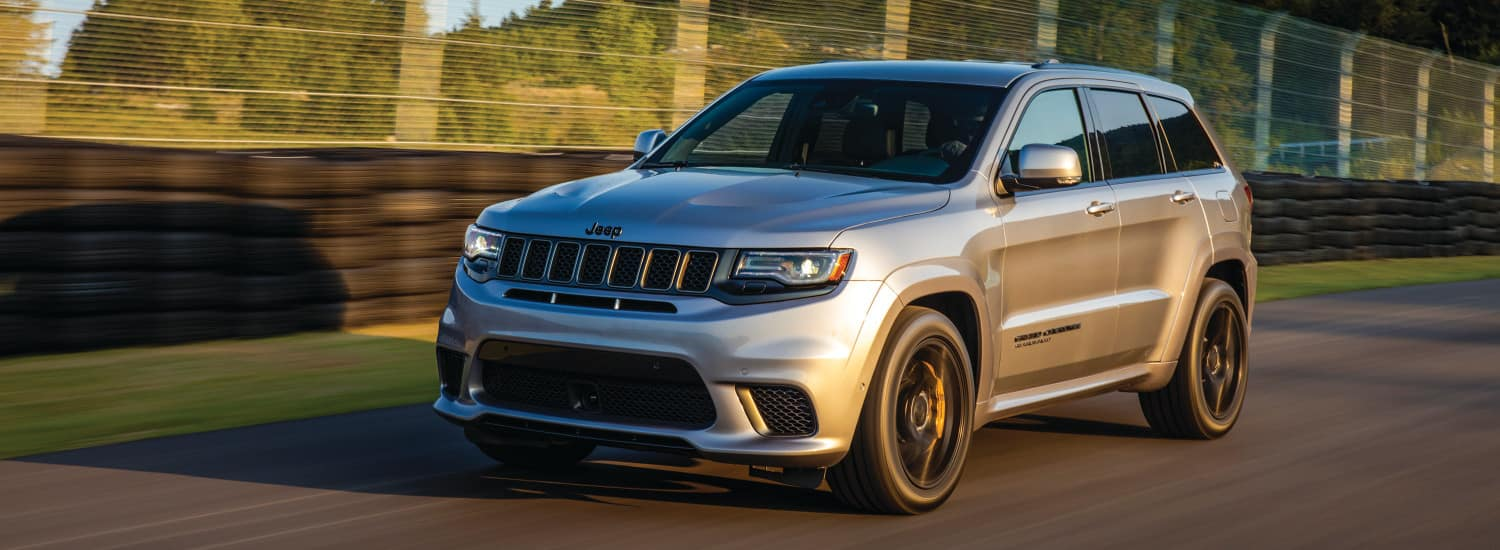 A silver 2018 Jeep Grand Cherokee driving on an open track