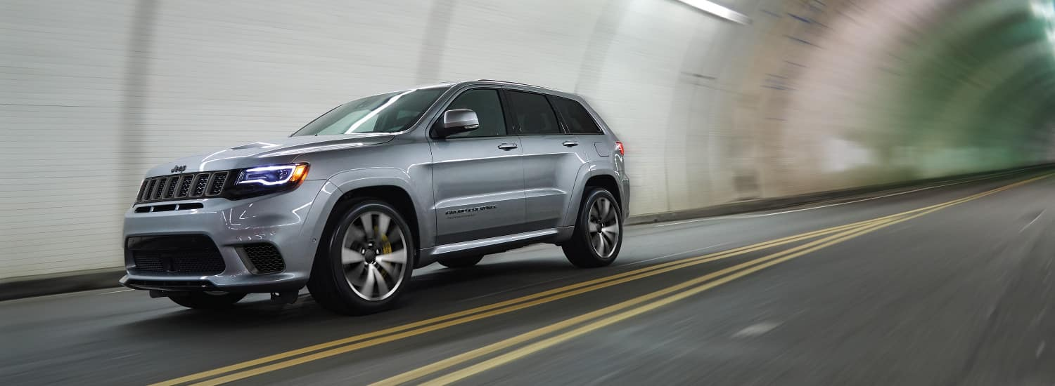 A silver 2018 Jeep Grand Cherokee driving through a tunnel