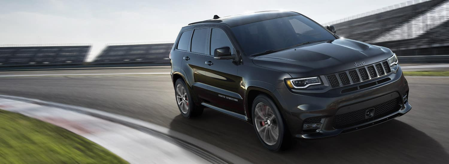 A black 2018 Jeep Grand Cherokee driving on an open track