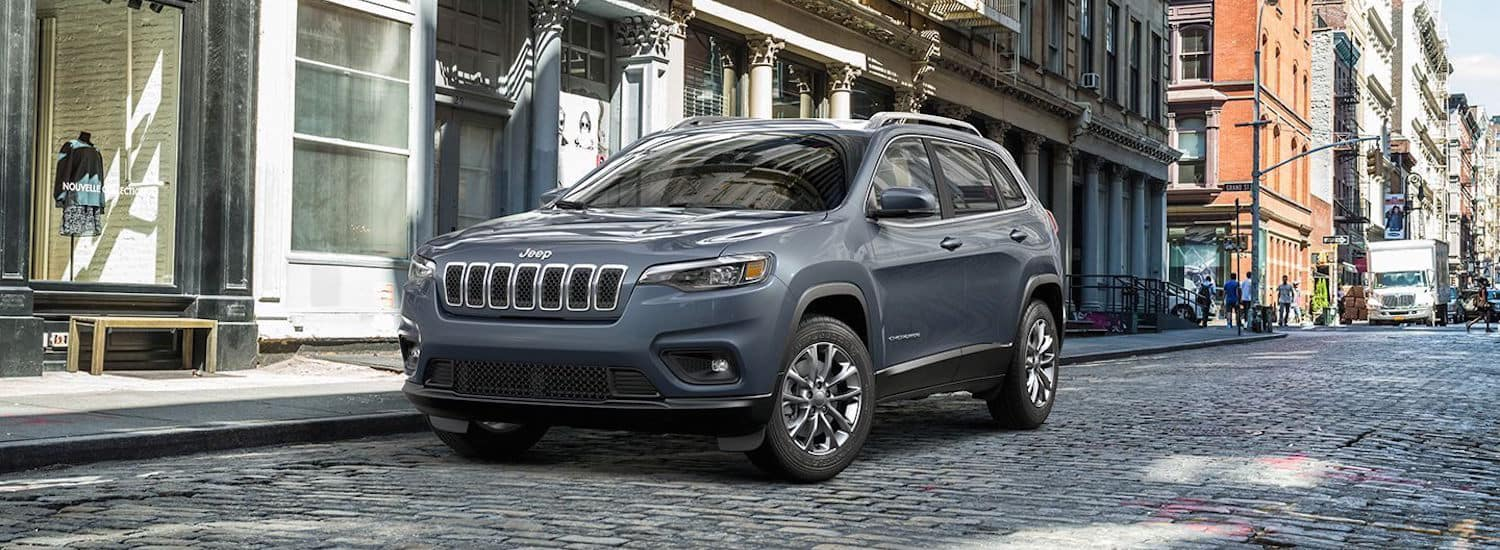 A silver 2019 Jeep Cherokee parked on a stone street