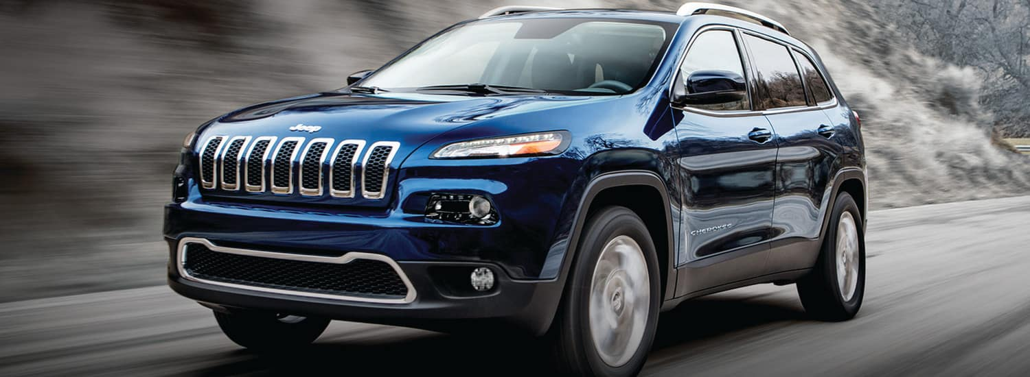 A blue 2019 Jeep Cherokee driving nature