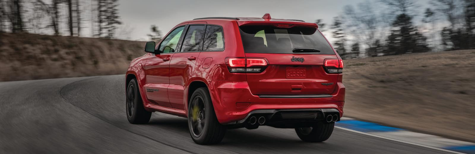 A red Jeep Grand Cherokee driving on a track