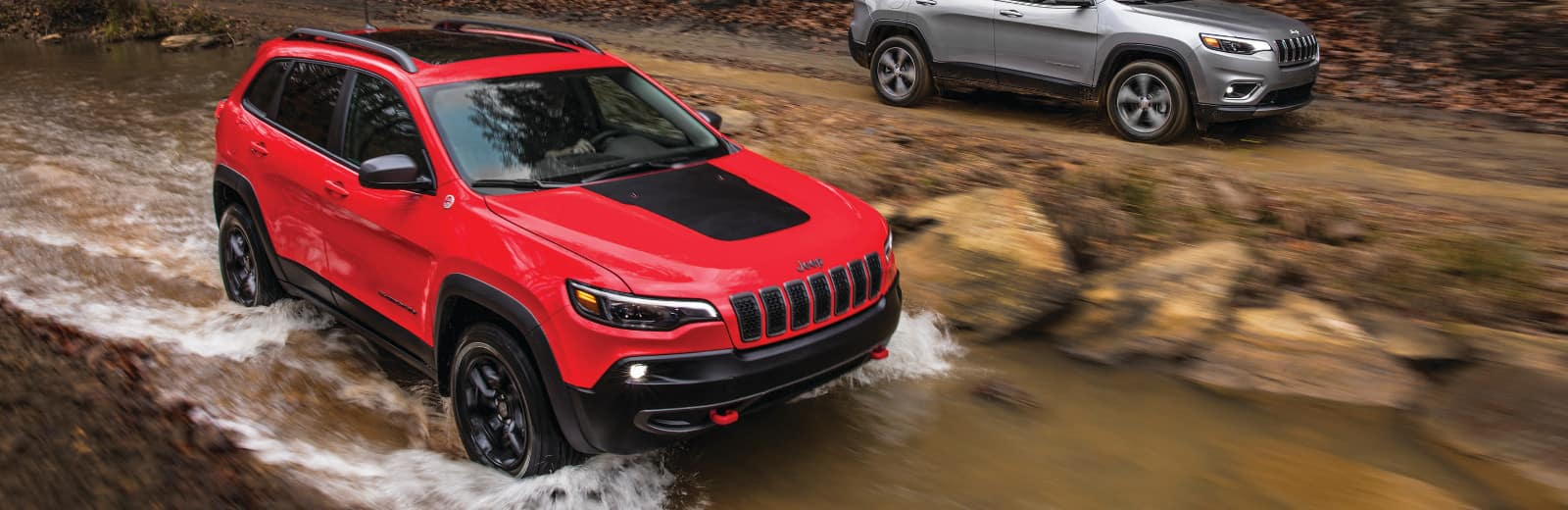 A red 2019 Jeep Cherokee driving through a river