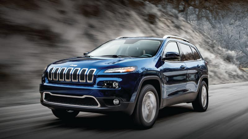 A blue 2019 Jeep Cherokee driving through the mountains